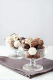 Choklader i exponeringsglas på den vita träbakgrunden Arkivfoton