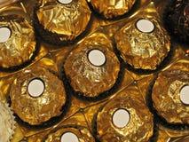 Choklader med rund form i guld- folie och vita små etiketter för text Fotografering för Bildbyråer