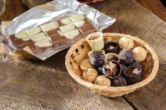 Choklader och choklad i en korg Arkivfoto
