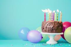 Chokladfödelsedagkaka med färgrika stearinljus arkivbild