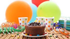Chokladfödelsedagkaka på den lantliga trätabellen med bakgrund av färgrika ballonger, gåvor, plast-koppar med godisar Royaltyfri Fotografi