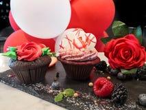 Chokladförälskelse dekorerade muffin med hjärtor och ballonger och rosor arkivfoton