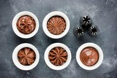 Chokladglasyren på kaka virvlar runt och den olika metallkonfektdysan Royaltyfri Fotografi