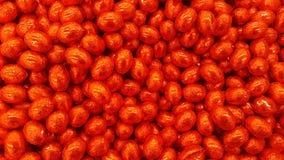 Chokladgodisägg som slås in i röd folie Fotografering för Bildbyråer