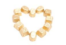 Chokladgodisar i papper för guld- folie som bildar hjärtan, formar arkivbilder
