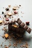 Chokladhus och torkade b?r med muttrar p? en svart bakgrund, vertikalt fotografering för bildbyråer