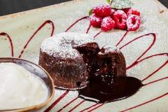 Chokladkaka eller fondant med hallon och vaniljglassboll på plattan, söt mat arkivbild