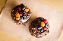 Chokladkaka med bär, träbakgrund Arkivfoton