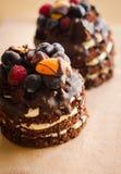 Chokladkaka med bär, träbakgrund Arkivbilder