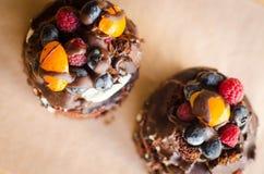 Chokladkaka med bär, träbakgrund Royaltyfria Foton