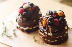 Chokladkaka med bär, träbakgrund Royaltyfri Bild