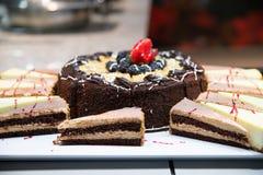Chokladkaka med ett snittstycke och blad på vit bakgrund Royaltyfria Foton