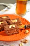 Chokladkaka med isläggning och kasjuer Arkivbild