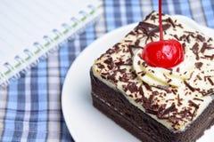 Chokladkaka med körsbäret och anteckningsboken Arkivfoto