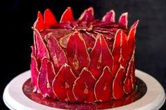 Chokladkaka med skivade röda päron med guld, som en krona på den svarta bakgrundsnärbilden Royaltyfria Bilder
