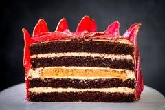 Chokladkaka med skivade röda päron med guld, som en krona på den svarta bakgrundsnärbilden Fotografering för Bildbyråer