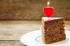 Chokladkaka med stearinljus i formen av en hjärta Royaltyfria Foton
