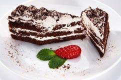 Chokladkaka på en vit platta med jordgubbar och mintkaramellen royaltyfri bild