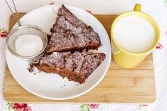 Chokladkakan i en vit platta och koppen med mjölkar Arkivfoto