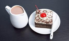 Chokladkakan med körsbäret och mjölkar tillbringaren Arkivfoton