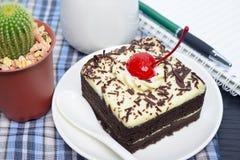 Chokladkakan med körsbäret och mjölkar tillbringaren, anteckningsbok Royaltyfria Bilder