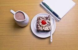 Chokladkakan med körsbäret och mjölkar tillbringaren, anteckningsboken, kaktus Royaltyfria Bilder