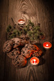 Chokladkakor med gran förgrena sig på en träbakgrund med stearinljus 1 royaltyfri foto