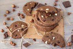 Chokladkakor med hasselnötter, vit choklad och mörkerchoklad på pergament, träbakgrund Royaltyfri Foto