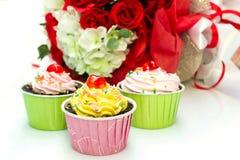 Chokladkakor och rosor på vit bakgrund Fotografering för Bildbyråer
