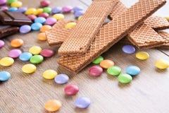 Chokladkex på trätabellen med färgsötsaker royaltyfria foton