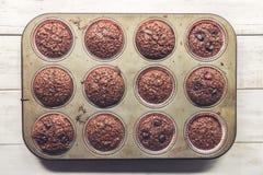 Chokladklimuffin med körsbär, i gammalt, grunge som ser, tenn- magasin arkivfoton