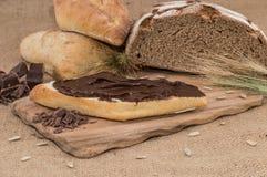 Chokladkräm på en bulle (lantlig bakgrund) Fotografering för Bildbyråer