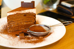 Chokladkräppkaka med pudrad choklad i den vita maträtten på th Royaltyfri Foto