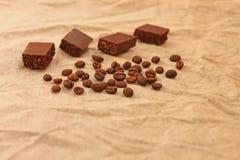 Chokladkuber med kaffeb?nor p? en linnetexturbakgrund royaltyfri foto