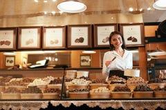 Chokladlager Den kvinnliga säljaren i konfekt shoppar arkivfoto