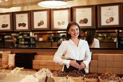 Chokladlager Den kvinnliga säljaren i konfekt shoppar royaltyfri bild
