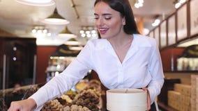 Chokladlager Den kvinnliga säljaren i konfekt shoppar stock video