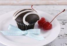 Chokladmuffin med festliga röda maraschinokörsbär Royaltyfri Bild