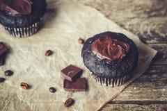 Chokladmuffin med isläggning på träbakgrund Royaltyfria Foton