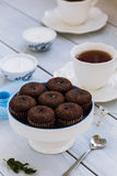 Chokladnissen och en kopp te på trätabellen Arkivbild