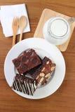 Chokladnissen på vitplattor med mjölkar royaltyfri fotografi