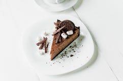 Chokladostkaka med stycken av choklad, kakor och marshmallowen p? en vit platta fotografering för bildbyråer