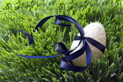 Chokladpåskägg med bandpilbågen i gräset Arkivbild