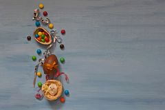 Chokladpåskägg och sötsaker på blå bakgrund royaltyfria bilder