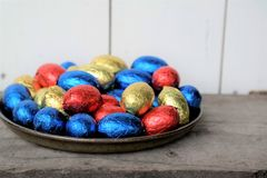 Chokladpåskägg, rött, blått och gult på en träyttersida Fotografering för Bildbyråer