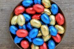 Chokladpåskägg, rött, blått och gult på en träyttersida, bästa sikt Arkivbild