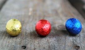 Chokladpåskägg som är röda som är blåa och som är gula på en träyttersida Arkivbilder