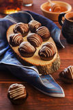 Chokladprofiteroles på ett träbräde Arkivbild