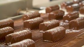 Chokladsötsaker på transportbandet arkivfilmer