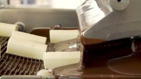 Choklads?tsaker p? transportbandet arkivfilmer